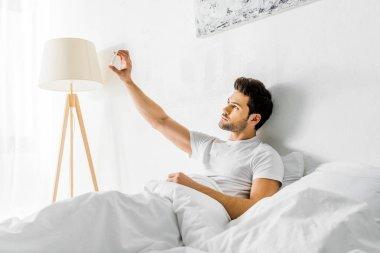 Handsome man taking selfie on smartphone in bedroom stock vector