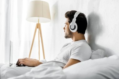 thoughtful man listening music with headphones and laptop in bed