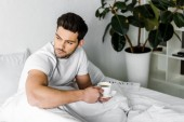 Fotografia thoughtful young man in pajamas holding cup of coffee in bed