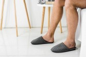 Photo cropped view on male legs in slippers in bedroom
