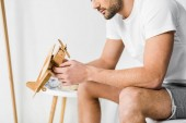 cropped view of man holding wooden toy airplane in bedroom