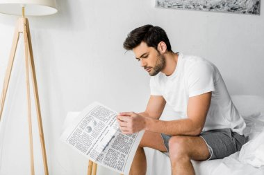handsome young man reading newspaper in bedroom