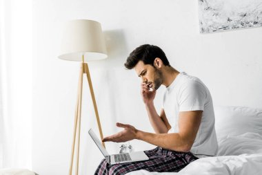Worried man talking on smartphone and using laptop on bed stock vector