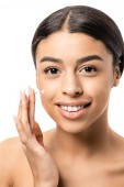 Fotografie close-up view of beautiful young african american woman applying face cream and smiling at camera isolated on white