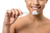 cropped shot of happy young african american woman holding toothbrush with toothpaste isolated on white