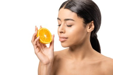 Beautiful naked african american woman with closed eyes holding half of orange near face isolated on white stock vector