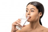 beautiful young african american woman drinking water from glass and looking away isolated on white