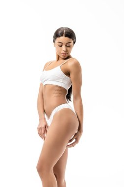 attractive african american girl in white underwear looking down at hip isolated on white