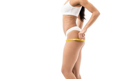 cropped shot of young african american woman in underwear measuring hips with tape isolated on white