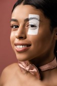 Photo beautiful young african american woman with bow tie and white paint on face smiling at camera isolated on brown