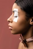 Fotografie side view of beautiful african american woman with white paint stroke on eye and bow tie isolated on brown
