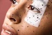 Fotografie Detailní pohled krásné ženské tváře s bílou barvou na oči a hnědé potřísnění izolovaných na hnědé