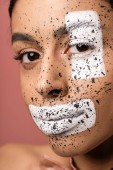 Fotografia beautiful african american woman with white paint and brown splashes on face looking at camera isolated on pink