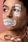 Fotografia bella donna afroamericana con vernice bianca e marrone spruzza il viso distogliendo lo sguardo isolato rosa