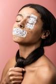 krásná africká americká žena s postříkání malování na obličej a vlasy kolem krku izolované na růžová