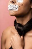 oříznuté záběr mladé afroamerické ženy s Malování na obličej a bruneta vlasy kolem krku izolované na růžové