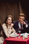 Fotografie beautiful woman sitting at table and smoking cigar while having romantic dinner with handsome man in restaurant