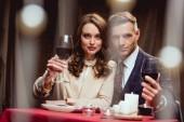 krásný pár držení sklenice červeného vína a při pohledu na fotoaparát během romantické rande v restauraci