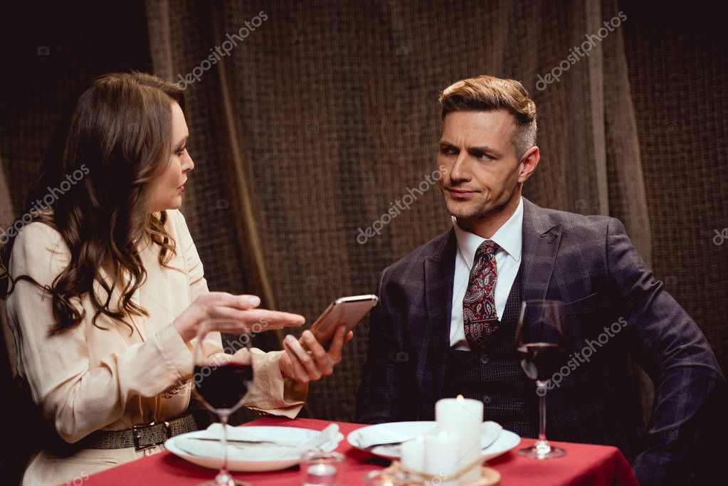 Woman holding smartphone and arguing with dissatisfied man during romantic date in restaurant