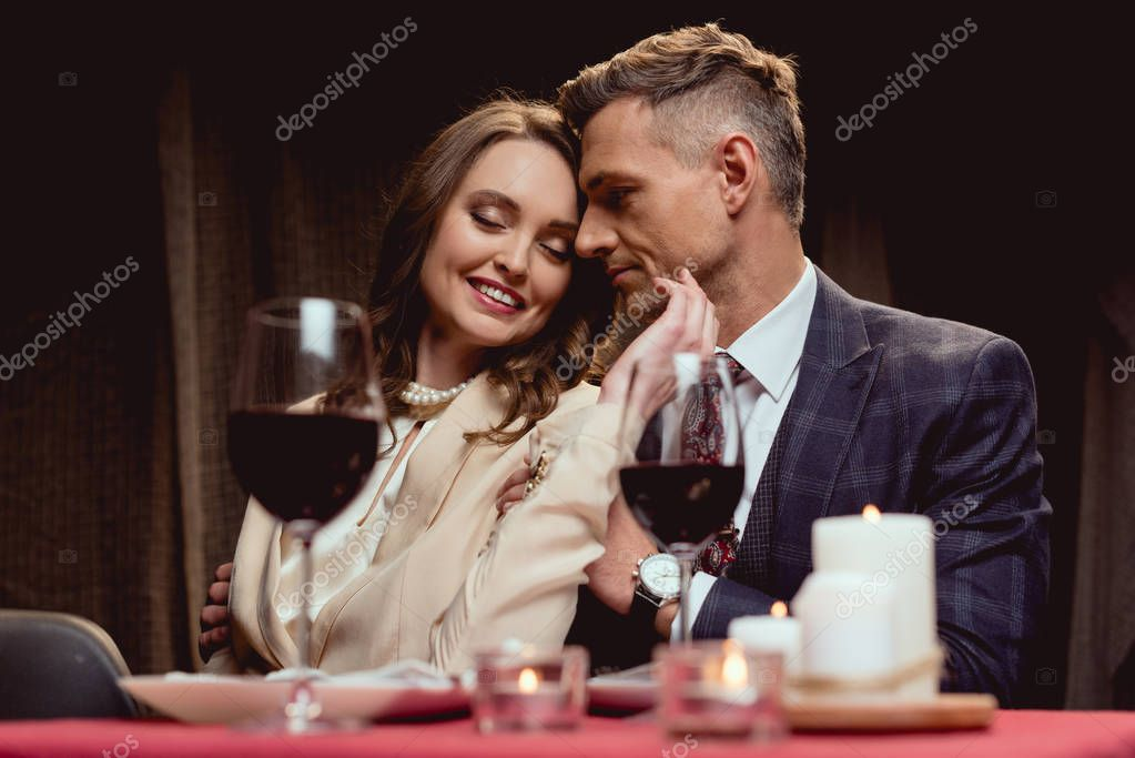 Beautiful smiling woman gently touching face of man during romantic date in restaurant stock vector