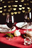 Fotografia selective focus of red wine glasses with heart shaped bokeh and table setting on background