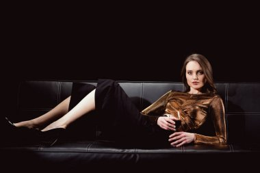 beautiful elegant woman lying on couch with glass of red wine and looking at camera isolated on black