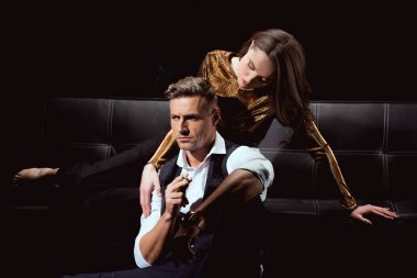 beautiful woman lying on couch and embracing handsome man with cigarette isolated on black