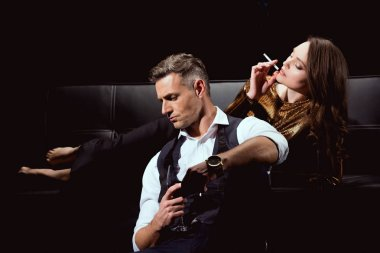 beautiful woman lying on couch with cigarette while handsome man holding glass of red wine isolated on black