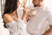 Photo woman feeding man with cereal during breakfast in morning