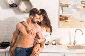 Fotografie Selektiver Fokus eines schönen sexy Paares, das sich in der heimischen Küche umarmt