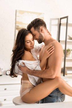 beautiful seductive couple passionately hugging at home