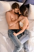 Fotografia beautiful sexy couple hugging and kissing in bed at home