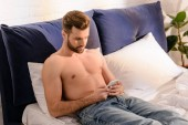 handsome shirtless man lying in bed and using smartphone at home in morning