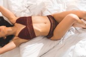Photo partial view of sexy woman in lingerie lying in bed at home in morning