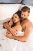 Fotografie krásné nahé pár všeobjímající během spánku v posteli