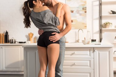 cropped view of young seductive couple passionately hugging in kitchen