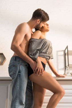 Selective focus of shirtless man passionately hugging woman in kitchen stock vector