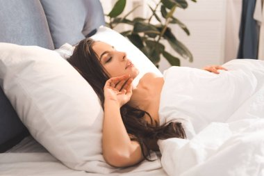 beautiful woman sleeping in bed at home in morning
