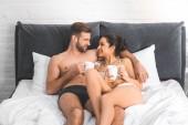 Fotografie schöne sexy Paar mit Kaffeetassen im Bett, lächelnd und sahen einander liegend