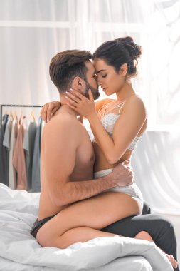 man embracing beautiful woman in white lingerie in bedroom