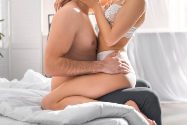 partial view of man embracing woman in white lingerie in bedroom