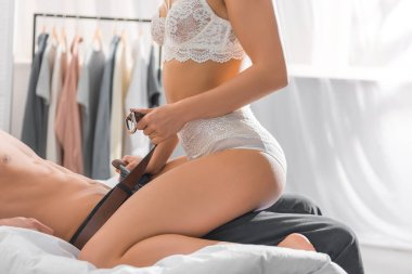 cropped view of woman in white lingerie undressing man during foreplay in bedroom
