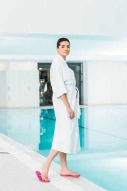 Attractive woman in bathrobe standing near swimming pool stock vector