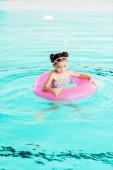 šťastné dítě plavání s nafukovací prstenec v bazénu