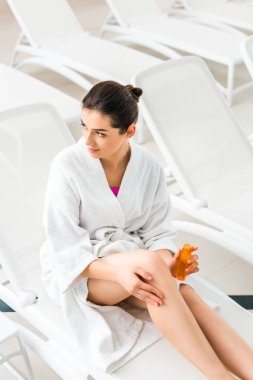 overhead view of beautiful woman applying body oil on leg while holding bottle