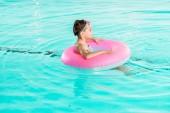 dítě v Googlu učení plavání s nafukovací prstenec v bazénu