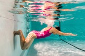Photo  woman diving underwater in pink swimsuit in blue water in swimming pool