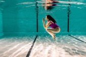 Fotografie attractive woman posing while diving underwater in swimming pool
