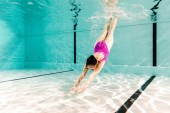 Fotografie woman diving underwater in swimming pool with blue water