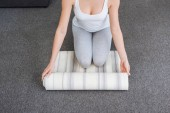 Fotografie cropped view of woman rolling fitness mat for practicing yoga at home
